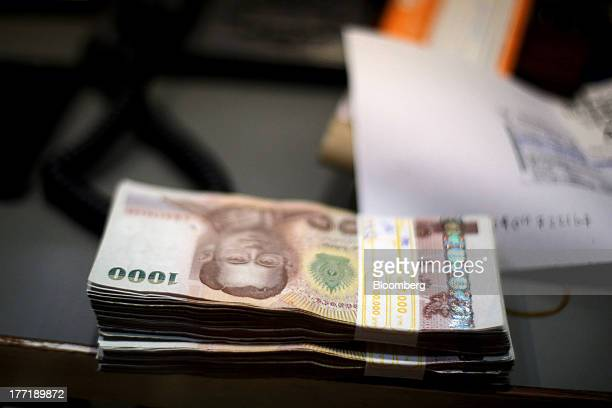 Bundles of Thai onethousand baht banknotes sit on a bench at a Super Rich 1965 Co currency exchange store in Bangkok Thailand on Thursday Aug 22 2013...
