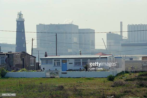 A bungalow on Dungeness Headland in Dungeness Kent UK with the old 1904 lighthouse in the background left 24th April 1998