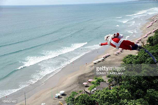 A bungee jumper dressed as Santa Claus leaps from a platform above Kuta beach Denpasar on Indonesia's resort island of Bali on December 2 2011 AFP...