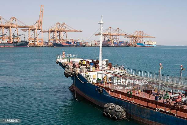 Bunkering tanker and freight cranes.