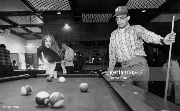 Bunny And Airman Pool Talents To Help Center Airman Maurice Forrest Syracuse NY looks on as Bunny Patti of the Denver Playboy Club makes a shot...
