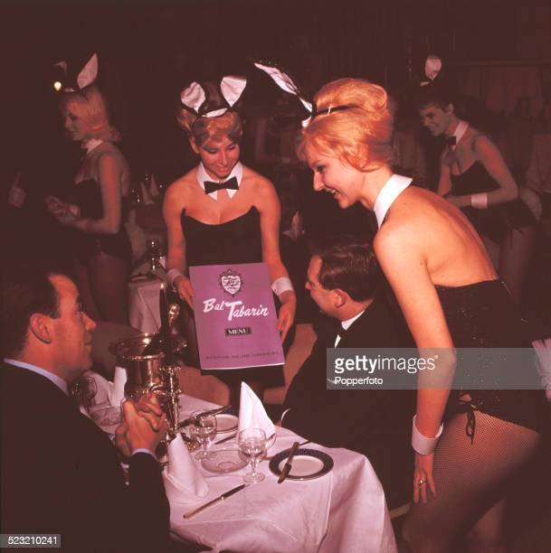 Bunny Girls present a menu to patrons in the dining area of Paul Raymond's Bal Tabarin Club and restaurant in London in 1963