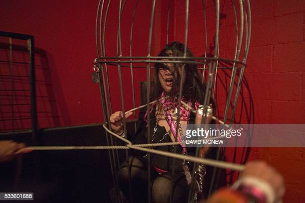 Bunny Lua Is tugged with a rope while caged at a dungeon party during the DomCon LA domination convention on May 22 2016 in Los Angeles California...