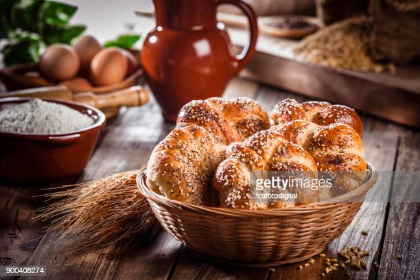 buns of bread with sesame and poppy seeds in a wicker basket - bun bread stock pictures, royalty-free photos & images