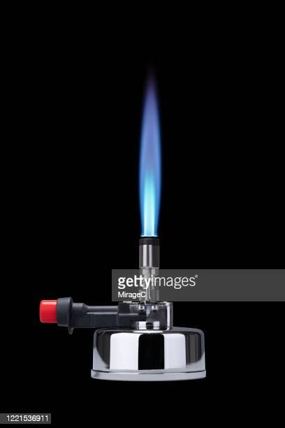 bunsen burner burning with blue flame - bunsen burner stock pictures, royalty-free photos & images