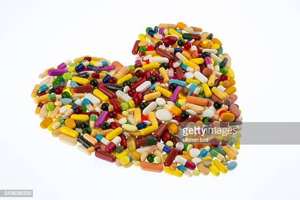 Bunte Tabletten in Herzform angeordnet Symbolfoto für Herzkrankheiten Medikation und Pharmazeutika