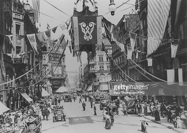 Bunting and flags decorate Friedrich Street in honour of the Jubilee of German Emperor Wilhelm II while below cars pass along the road with crowds of...