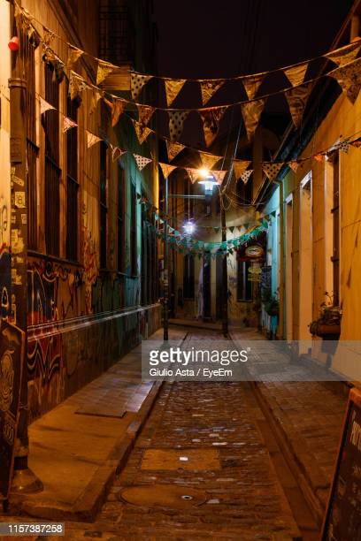 buntings hanging in illuminated alley amidst buildings at night - valparaiso chile stock pictures, royalty-free photos & images