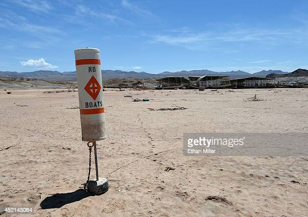 A buoy warning 'no boats' stands on dirt at the abandoned Echo Bay Marina on July 13 2014 in the Lake Mead National Recreation Area Nevada The marina...