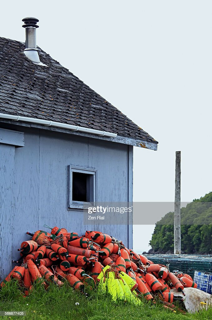 Buoys piled up against a storage building : Stock-Foto