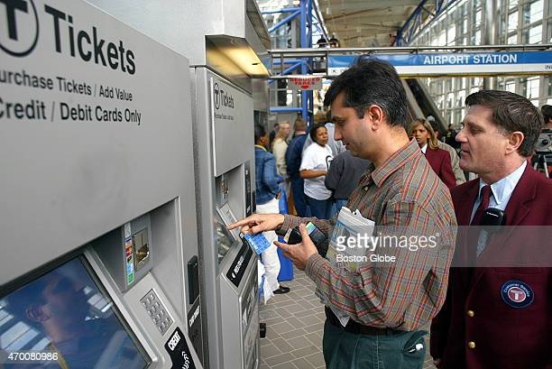 Bupendra Sharma uses a credit card to buy a Charlie ticket as one of the new MBTA Customer Service Agents Matthew Powers right looks over his...