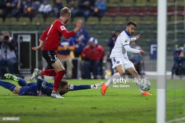 Burak Camoglu of Karlsruhe scores his team's first goal past Michael Vitzthum and goalkeeper Kevin Broll of Grossaspach during the 3 Liga match...