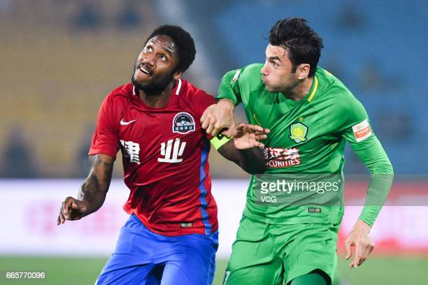 Burak Yilmaz of Beijing Guoan and Eddi Gomes of Henan Jianye compete for the ball during the 4th round match of China Super League between Beijing...