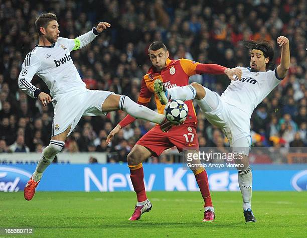 Burak Yilmaz of Galatasaray is challenged by Sergio Ramos and Sami Khedira of Real Madrid during the UEFA Champions League Quarter Final first leg...