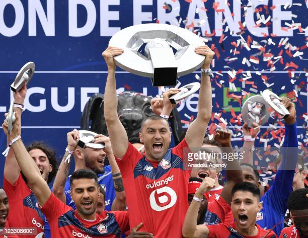 Burak Yilmaz of Lille holds French Ligue 1 Trophy next to Zeki Celik and Luis Araujo during the French Ligue Trophy ceremony at the Domaine de Luchin...