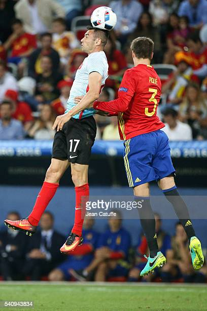 Burak Yilmaz of Turkey and Gerard Pique of Spain in action during the UEFA EURO 2016 Group D match between Spain and Turkey at Allianz Riviera...