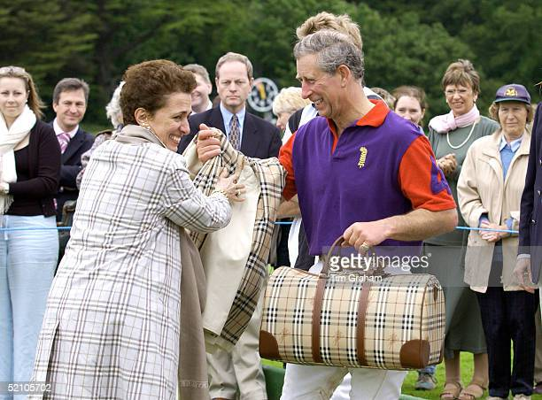 Burberry Chief Rose Marie Bravo Presenting Prizes Of A Burberry Raincoat And Bag To Prince Charles After A Charity Match To Raise Funds For...