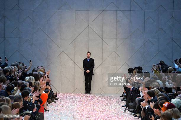 Burberry Prorsum's designer Christopher Bailey greets the audience at the end of the 2014 Spring/Summer catwalk show during the London Fashion Week...