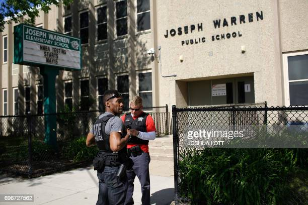 A Bureau of Alcohol Tobacco Firearms agent and a Chicago Police officer stand outside Warren Elementary School where two girls 7 and 13 were shot...