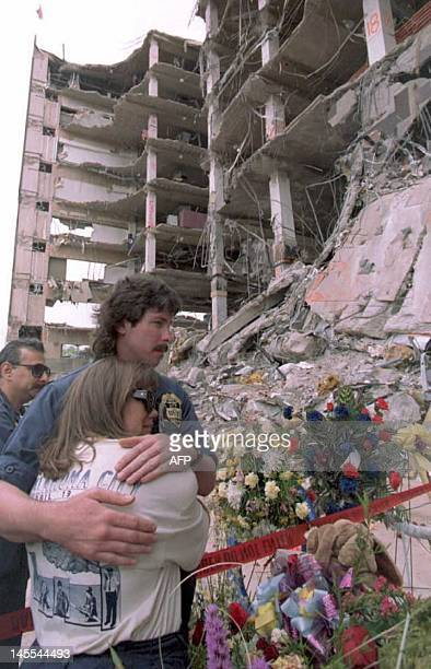 Bureau of Arms Tobacco and Firearms agent Luke Franey hugs Oklahoma city ATF Bureau manager Valerie Rauden in front of the remains of the Alfred P...
