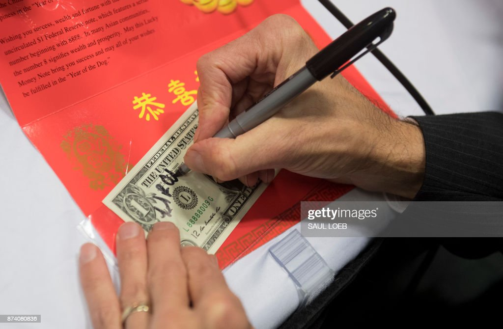 Bureau of Engraving and Printing (BEP) Director Leonard Olijar signs the Year of the Dog 2018 product in celebration of the Chinese Lunar New Year, featuring a $1 Federal Reserve note with a serial number beginning with '8888', during a press conference at the Bureau of Engraving and Printing in Washington, DC, November 14, 2017. /