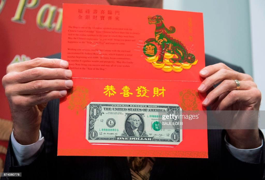 Bureau of Engraving and Printing (BEP) Director Leonard Olijar unveils the Year of the Dog 2018 product in celebration of the Chinese Lunar New Year, featuring a $1 Federal Reserve note with a serial number beginning with '8888', during a press conference at the Bureau of Engraving and Printing in Washington, DC, November 14, 2017. /