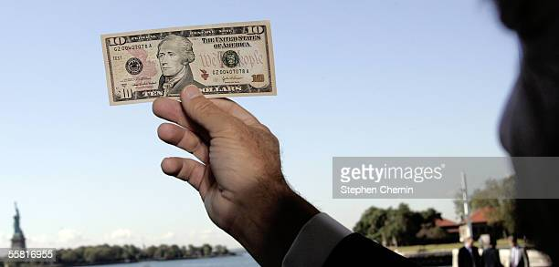 S Bureau of Engraving and Printing Director Thomas Ferguson holds the new $10 bill up to the light to reveal security printing during it's unveiling...