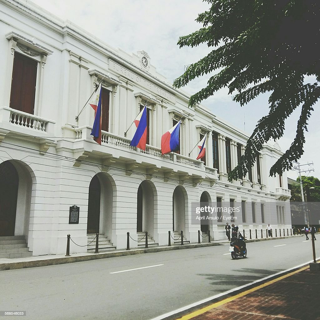 Bureau Of The Treasury Building With Flags Hanging In City : Stock Photo