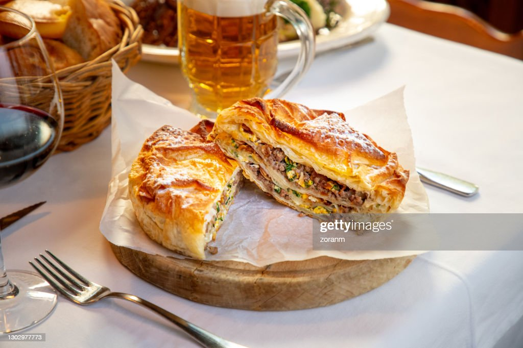 Burek with minced meat and other ingredients cut in half, rustic place setting : Stock Photo