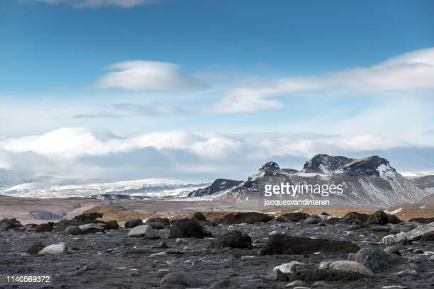 burfell volcano and mydalsjokull (glacier) in the background as seen from the beach of reynisfjara - basalt stock pictures, royalty-free photos & images