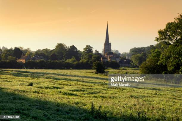 Burford church spire, by the banks of the River Windrush, sunset, in the Cotswolds