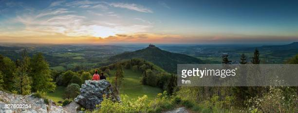 burg hohenzollern (hohenzollern castle) with an unrecognizable couple watching the sunset - panorama (baden-württemberg/ germany) - baden württemberg stock-fotos und bilder