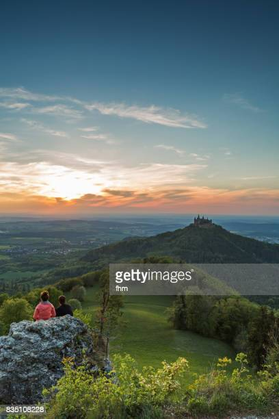 Burg Hohenzollern (Hohenzollern Castle) with an unrecognizable couple watching the sunset - panorama (Baden-Württemberg/ Germany)