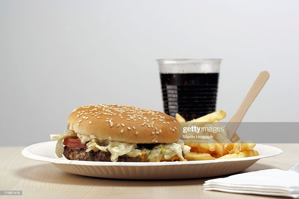 Burger and french fries on paper plate next cup of cola : Stock Photo