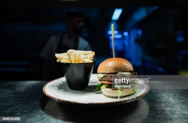 A burger and fries stands on the pass at a Bar and Block restaurant operated by Whitbread Plc in London UK on Wednesday Jan 17 2018 The hotel and...