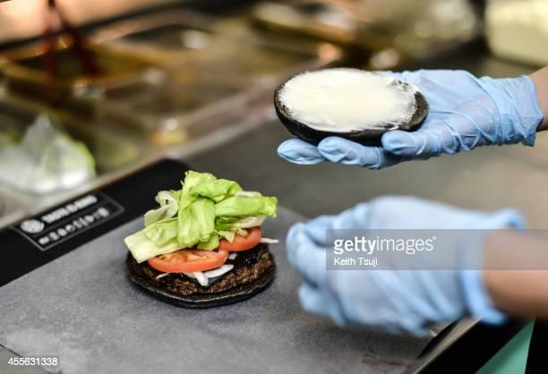 Burger King employee prepares a black burger at a company restaurant on September 18 2014 in Tokyo Japan The black burgers one a Kuro Pearl at 480...