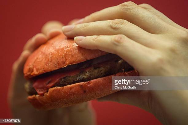 Burger King employee shows off the new 'Red' burger at a store on June 22 2015 in Tokyo Japan The AKA Samurai Burger and the Samurai Chicken Burger...