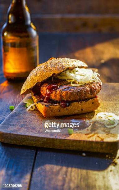 burger on wooden board next to beer bottle - barbeque sauce stock photos and pictures