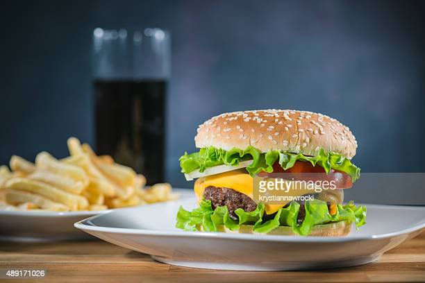 Hamburguesa se sirven en un plato con papas fritas y una cola
