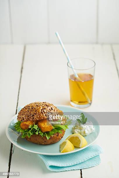 Burger with fish fingers and herb curd on plate