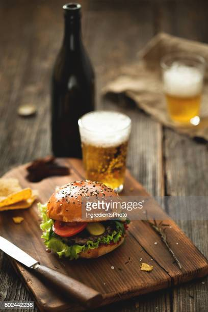 Burger with salad and glass of beer on wooden table.