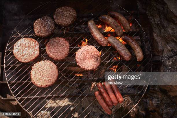 burgers and sausages cooking on campfire - heshphoto stock pictures, royalty-free photos & images