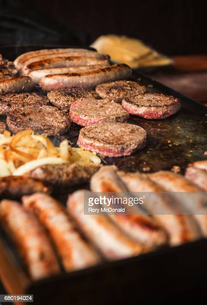 Burgers and sausages on a stall at a farmer's market.