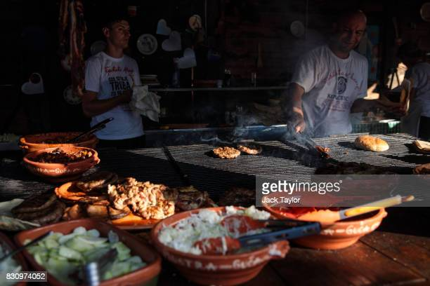 Burgers are cooked on a grill during the Guca Trumpet Festival on August 10 2017 in Guca Serbia Thousands of revellers attend the trumpet festival...