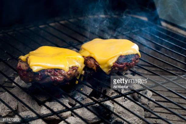 burgers on charcoal grill - cheeseburger stock pictures, royalty-free photos & images