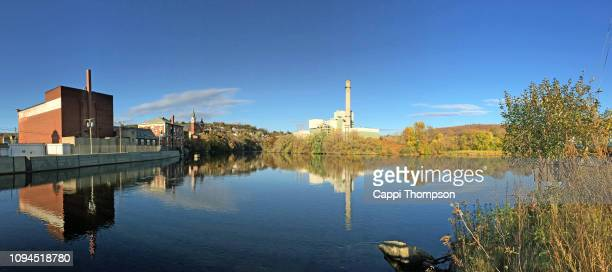 burgess bio power plant in berlin, new hampshire usa with androscoggin river in view during autumn - incinerator stock photos and pictures