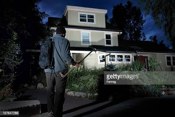 burglar approaching a home at night - burglar stock pictures, royalty-free photos & images