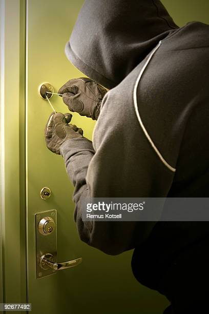 Burglar breaking into a house by picking a lock