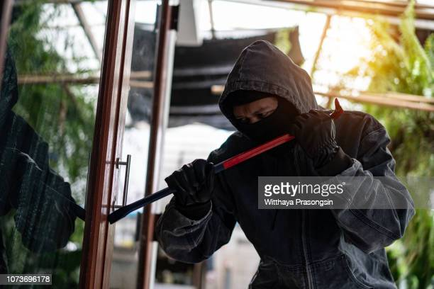 burglar breaking into a house via a window with a crowbar - burglar stock pictures, royalty-free photos & images