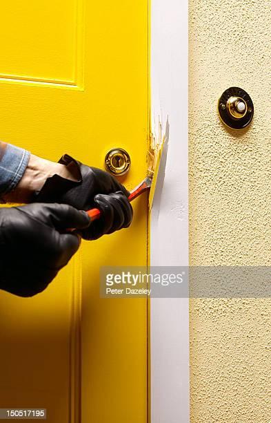 Burglar breaking into the front door of a house